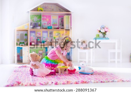 Little girl playing. Kids with doll house and stuffed animal toys. Children sit on a pink rug in a play room at home or kindergarten. Toddler kid with plush toy and dolls. Birthday party for child. - stock photo
