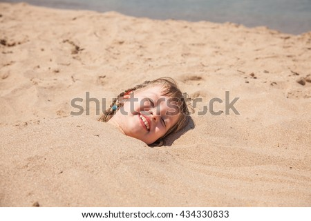 Little girl playing on the beach while hiding her body in the sand. Only the head stick out of the sand. Family fun, summer time. Selective focus. - stock photo