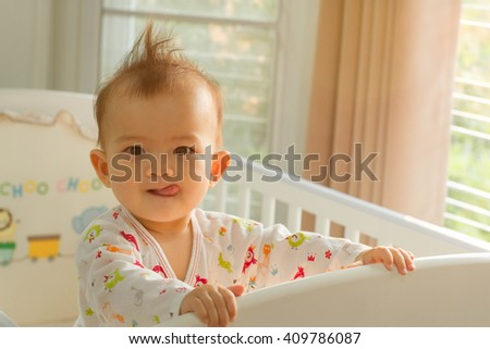 little girl playing on the bed in morning - stock photo