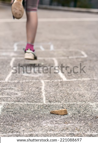 Little girl playing on the hopscotch - stock photo