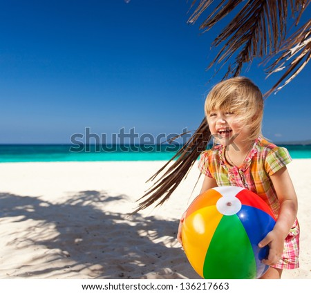 Little girl playing on tropical beach with ball - stock photo