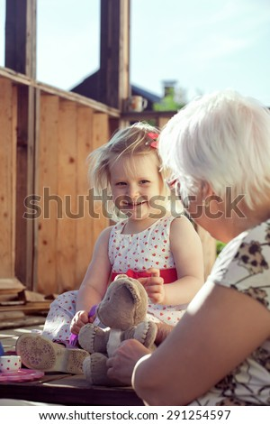 Little girl playing tea time with her grandmother on country house doorsteps in summer. Natural outdoor light setting. Focus is on the girl. Toned photo. - stock photo