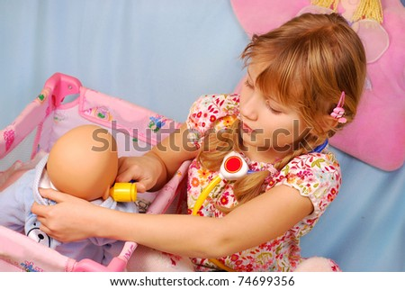 little girl playing the doctor with her newborn baby doll in room - stock photo