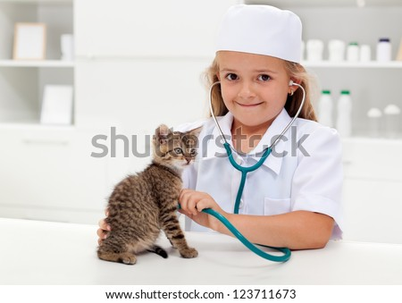 Little girl playing veterinary with her kitten - animal care concept - stock photo