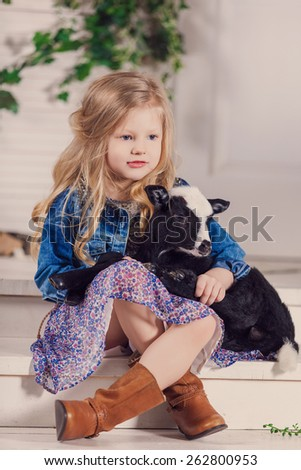 Little girl playing with a baby goat on a house porch - stock photo