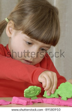 Little girl playing with a clay - stock photo