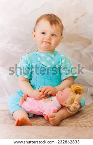 little girl playing with a doll - stock photo
