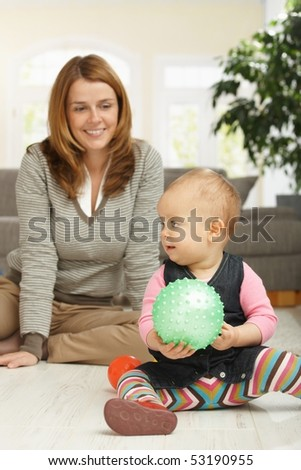 Little girl playing with ball sitting on living room floor, mum in background looking happy. - stock photo