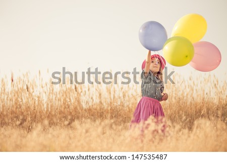 Little girl playing with balloons on wheat field - stock photo