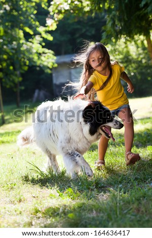 Little girl playing with best friend in summer garden - stock photo