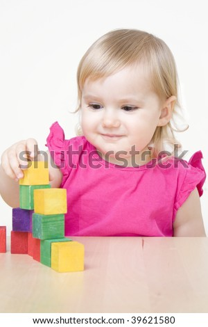 Little girl playing with bricks - stock photo