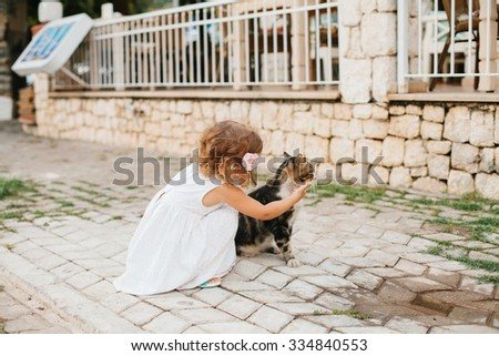 Little girl playing with cat outdoor - stock photo