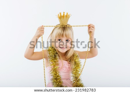 little girl playing with Christmas tinsel - stock photo
