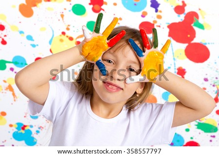 Little girl playing with colors, girl showing painted hands - stock photo