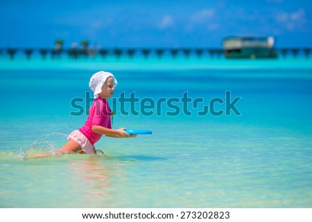 Little girl playing with flying disc at wnite beach - stock photo