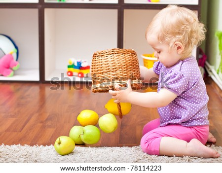 little girl playing with fresh fruit in her room - stock photo