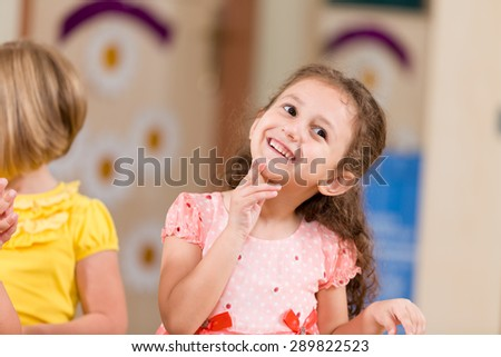 Little girl playing with her friends. - stock photo