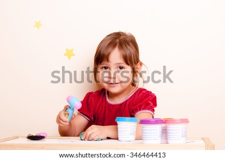 little girl playing with plasticine - stock photo
