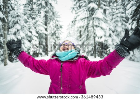 Little Girl Playing with Snow Outdoors in Winter - stock photo