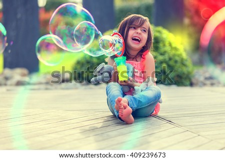 Little girl playing with soap bubbles machine - stock photo