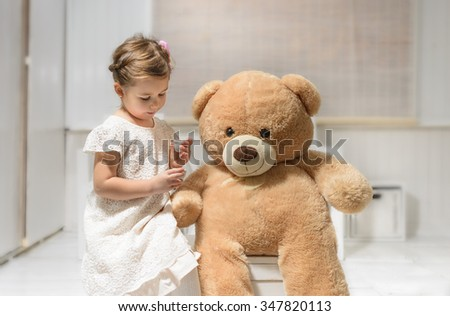 Little girl playing with teddy bear. Expressive beautiful little girl having a tea party with her teddy bear.  - stock photo
