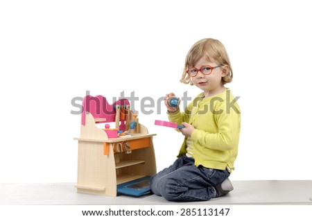 little girl playing with wooden kitchen toys, isolated on white - stock photo