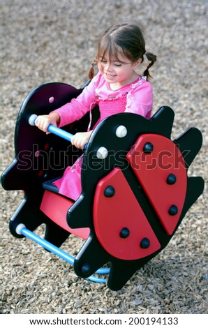 Little girl plays on a swing in a shape of Ladybird in modern children toy playground in a park. - stock photo
