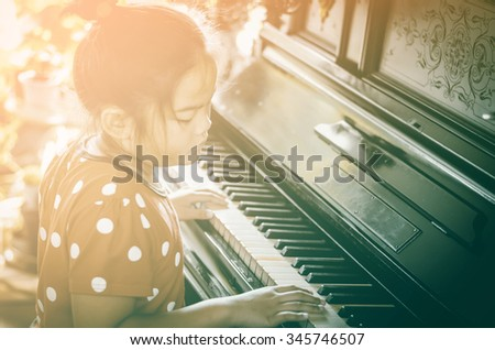 Little girl plays piano, Bright and vintage process - stock photo
