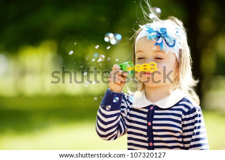 little girl plays with bubbles - stock photo