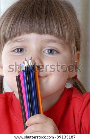 Little girl portrait drawing and playing with a crayon. - stock photo