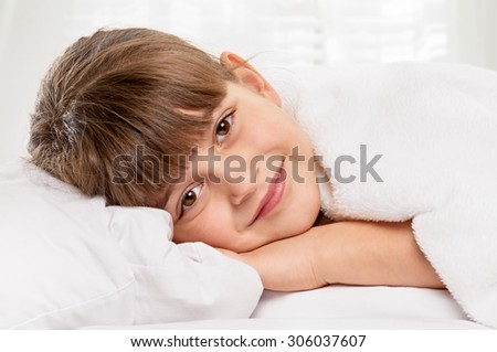Little girl portrait on pillow in bed with light window background - stock photo