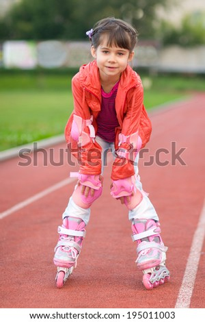 Little girl portrait summer outdoors on the rollers   - stock photo