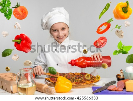 little girl pour pizza with ketchup on kitchen table with flying food ingregients - stock photo