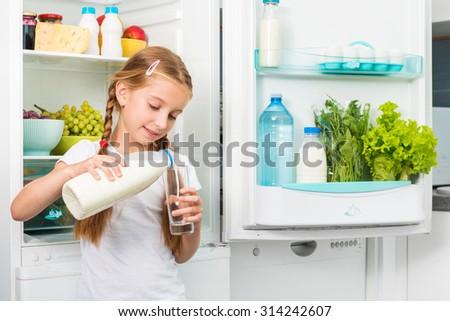 little girl pouring milk in glass near opened fridge - stock photo