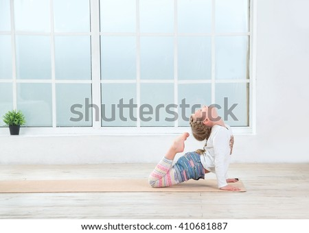 Little girl practicing yoga poses. Cute little girl do fitness exercise. Copy space. - stock photo