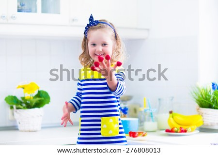 Little girl preparing breakfast in kitchen. Healthy food for children. Child drinking milk and eating fruit. Happy preschooler kid enjoying morning meal, cereal, banana and raspberry. Kids cooking. - stock photo
