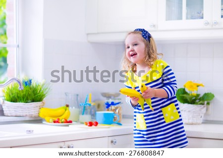 Little girl preparing breakfast in kitchen. Healthy food for children. Child drinking milk and eating fruit. Happy preschooler kid enjoying morning meal, cereal, banana and strawberry. Kids cooking. - stock photo