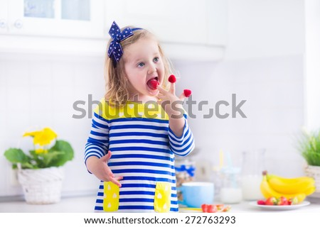 Little girl preparing breakfast in white kitchen. Healthy food for children. Child drinking milk and eating fruit. Happy smiling preschooler kid enjoying morning meal, cereal, banana and raspberry. - stock photo