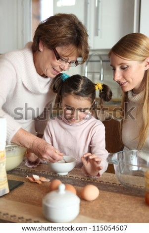 Little girl preparing cake with her mother and her grandmother - stock photo