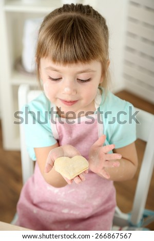 Little girl preparing cookies in kitchen at home - stock photo