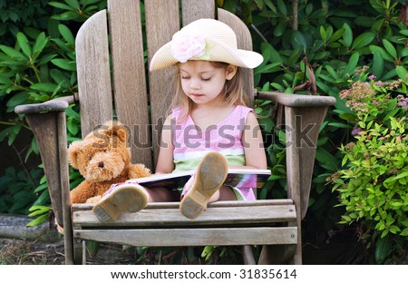 Little girl pretending to read to her teddy bear - stock photo