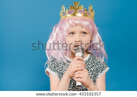 little girl princess singing with a microphone - stock photo