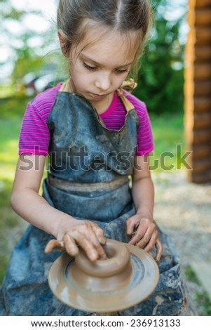 Little girl produced on potters wheel pot. - stock photo