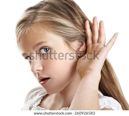 Little girl putting hand to her ear to hear better. - stock photo