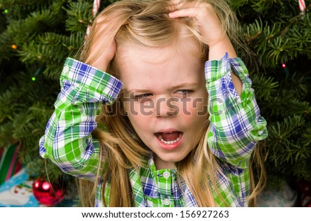 Little girl quite unhappy and distraught over getting the wrong gift. - stock photo