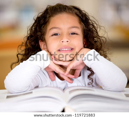Little girl reading a book at the library - stock photo