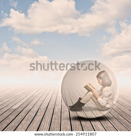 little girl reading a book inside a bubble on a wharf - stock photo