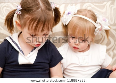 little girl reading a book sister - stock photo