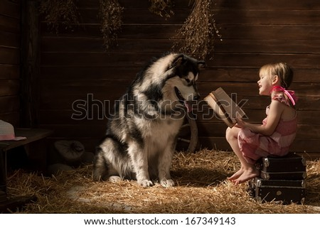 Little girl reading a book to his dog in the barn - stock photo