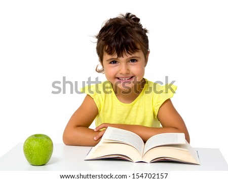 little girl reading a book with apple isolated on white - stock photo